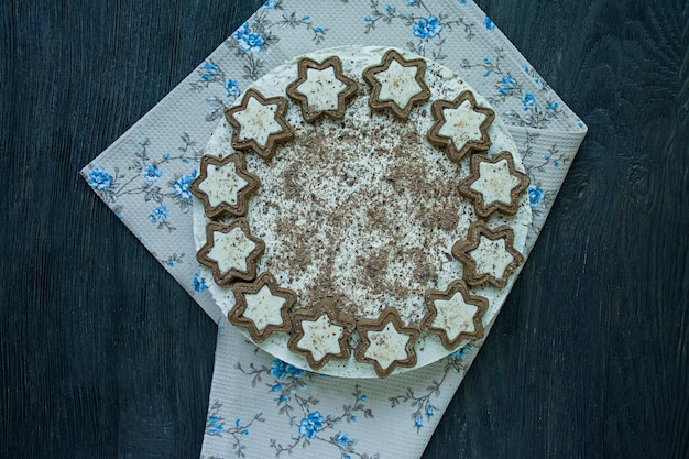 Cottage cheese cake is decorated with cookies and grated black chocolate on dark wood
