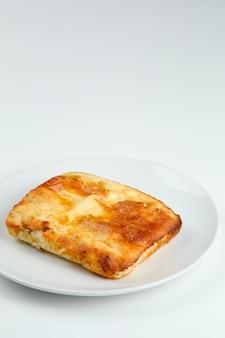 복사 공간이 있는 하얀 접시 근접 촬영에 있는 코티지 치즈 캐서롤. 코티지 치즈 캐서롤 절연 옴 흰색입니다.