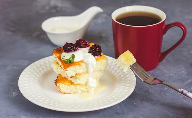 Творожная запеканка на белой тарелке и чай в бордовой чашке на сером фоне
