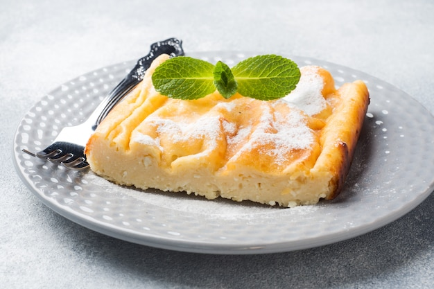 Cottage cheese casserole on a plate with powdered sugar and mint leaves.