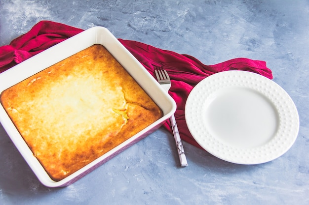 Cottage cheese casserole on a white plate and tea in a burgundy cup on a gray background