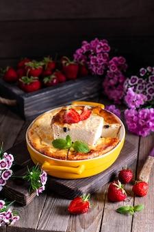 木製の背景のベーキング皿にレーズンとイチゴとカッテージチーズのキャセロール。健康的な朝食