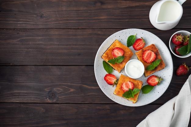 イチゴとミントのカッテージチーズのキャセロール。豆腐と新鮮なベリーとクリームで作ったおいしい自家製デザート。暗い木製の背景、コピースペース。
