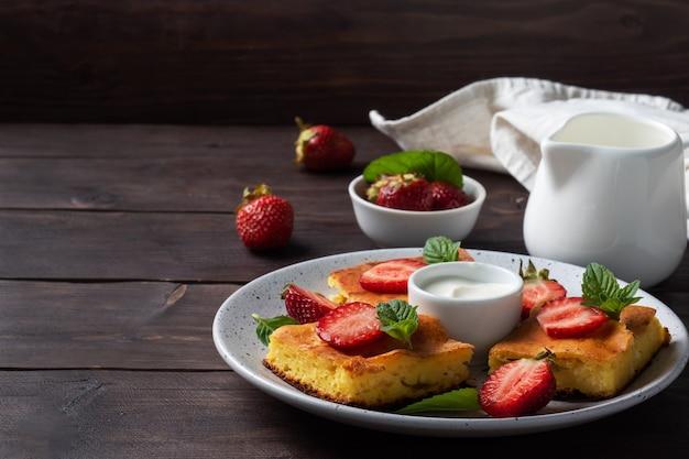 딸기와 민트를 곁들인 코티지 치즈 캐서롤. 커드와 신선한 베리로 만든 맛있는 수제 디저트와 크림. 어두운 나무 배경, 복사 공간입니다.