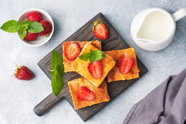 イチゴとミントのカッテージチーズのキャセロール。豆腐と新鮮なベリーとクリームで作ったおいしい自家製デザート。灰色のコンクリートの背景をクローズアップ。