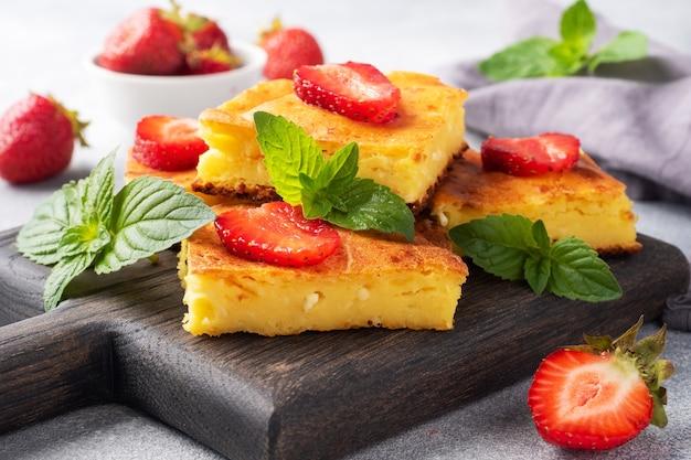 딸기와 민트를 곁들인 코티지 치즈 캐서롤. 커드와 신선한 베리로 만든 맛있는 수제 디저트와 크림. 회색 콘크리트 배경을 닫습니다.