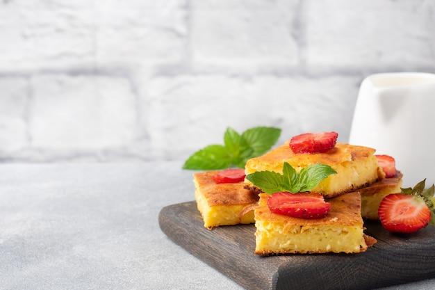 イチゴとミントのカッテージチーズのキャセロール。豆腐と新鮮なベリーとクリームで作ったおいしい自家製デザート。灰色のコンクリートの背景、コピースペース。