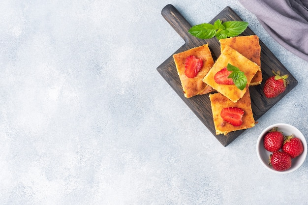 딸기와 민트를 곁들인 코티지 치즈 캐서롤. 커드와 신선한 베리로 만든 맛있는 수제 디저트와 크림. 회색 콘크리트 배경, 복사 공간입니다.