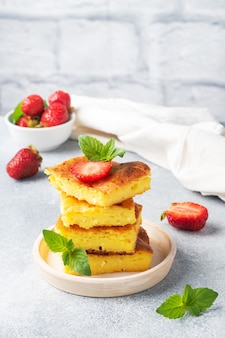 Cottage cheese casserole with strawberries and mint. delicious homemade dessert made of curd and fresh berries with cream. copy space