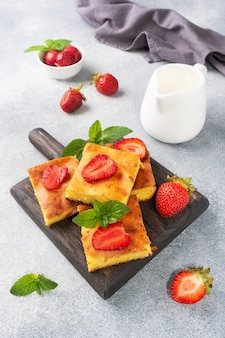 Cottage cheese casserole with strawberries and mint. delicious homemade dessert made of curd and fresh berries with cream. gray concrete background, copy space.