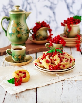 Cottage cheese cookie rolls with red currants on ceramic plate with vintage ceramic tea or coffee set, tea time, breakfast, summer sweets