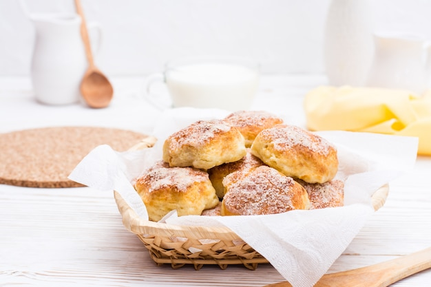 Cottage cheese cookies sprinkled with sugar in a basket and a cup of milk on a wooden table