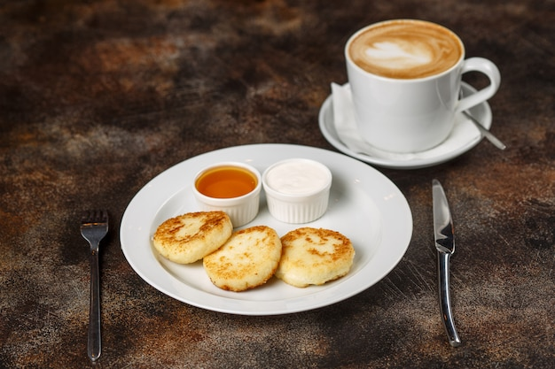 Cottage cheese curd pancakes or fritters with latte coffee