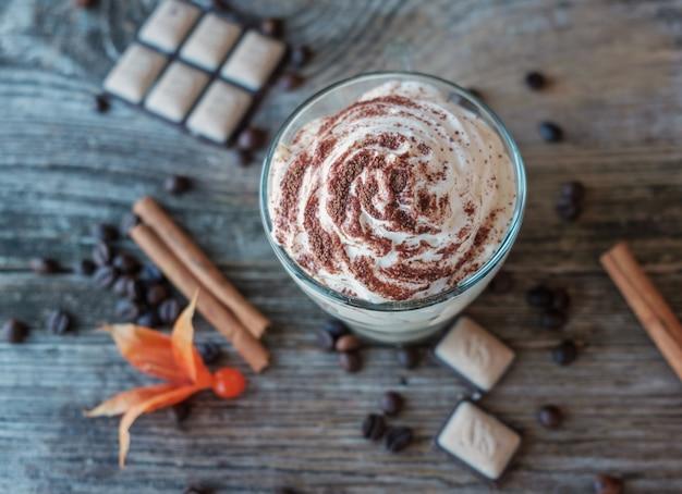 Творожный десерт тирамису в стакане, корица, шоколад, кофе и капский крыжовник на старой деревянной доске