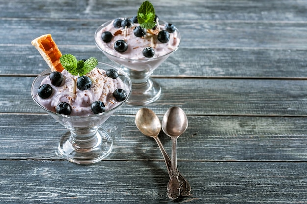 Cottage cheese dessert with blueberries and slices of viennese waffles in a glass cup.