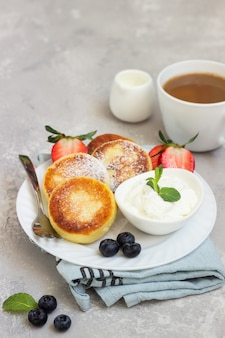Cottage cheese fritters (syrniki) served with sour cream, fresh berries (strawberry and blueberry) and mint. healthy breakfast or diet lunch.