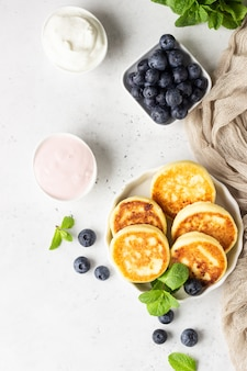 Cottage cheese fritters with blueberries, mint and sauce.