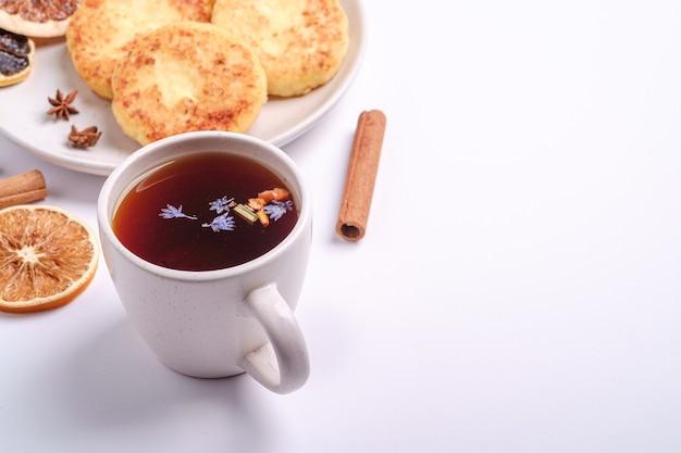 Творожные оладьи с горячим черным ароматным чаем, настроение рождественского завтрака с анисом и корицей на белом фоне, угол обзора копией пространства
