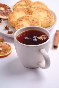 Творожные оладьи с горячим черным ароматным чаем, настроение рождественского завтрака с анисом и корицей на белом фоне, угловой вид