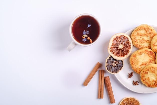 Творожные оладьи с горячим черным ароматным чаем, настроение рождественского завтрака с анисом и корицей на белом фоне, вид сверху копией пространства