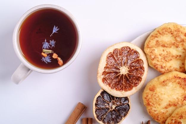 Творожные оладьи с горячим черным ароматным чаем, настроение рождественского завтрака с анисом и корицей на белом фоне, вид сверху