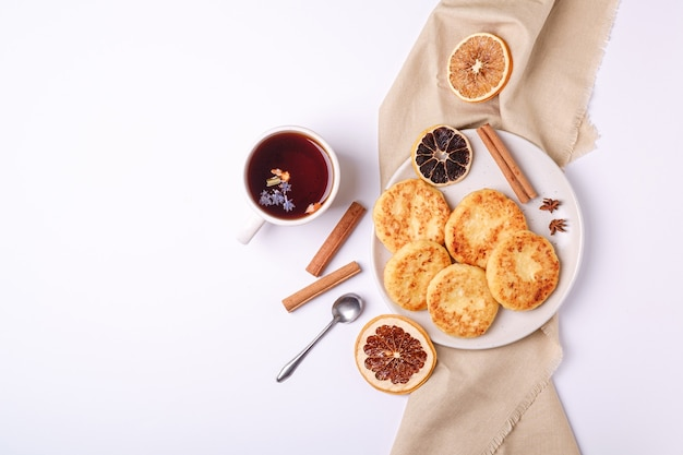Творожные оладьи с горячим черным ароматным чаем, настроение рождественского завтрака с анисом и корицей на белой поверхности, вид сверху