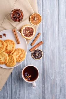 ホットブラックアロマティー、アニス、シナモン、木製の背景に乾燥した柑橘類とクリスマスの朝食ムード、上面図とカッテージチーズのフリッター