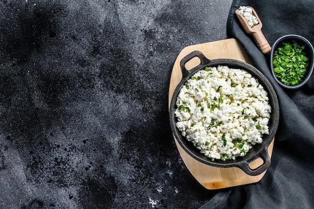Творог в чугунной посуде с зеленью. органические молочные продукты. черный фон. вид сверху. скопируйте пространство.