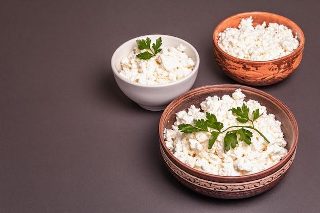 セラミックボウルのカッテージチーズ。深皿に自家製乳製品。石のコンクリートの背景、コピースペース