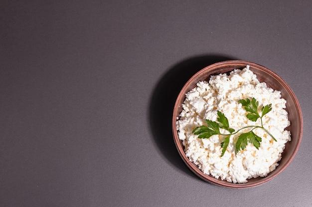 セラミックボウルのカッテージチーズ。深皿に自家製乳製品。石のコンクリートの背景、上面図、フラットレイ