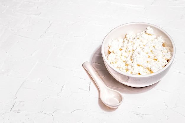 セラミックボウルのカッテージチーズ。深皿に自家製乳製品。白いパテの背景、コピースペース