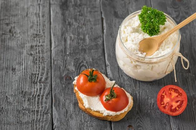 テーブルの上にパンとチェリートマトが入った瓶に入ったカッテージチーズ。健康的な食事の概念。