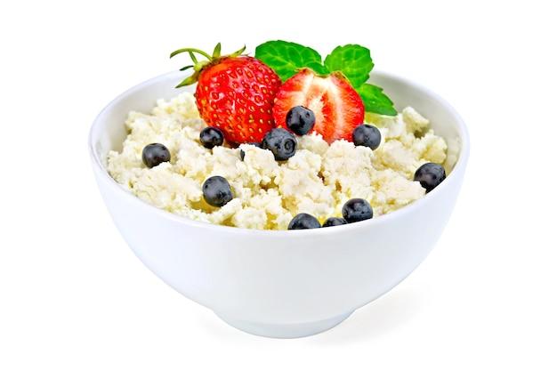 흰색 배경에 분리된 딸기, 블루베리, 민트가 있는 흰색 그릇에 코티지 치즈