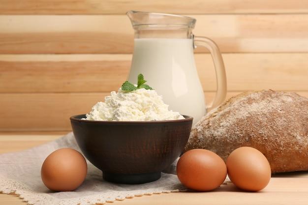 Творог в глиняной миске с кувшином для молока, буханкой хлеба и яйцами на деревянных досках