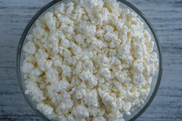 배경, 평면도의 유리 그릇에 코티지 치즈를 닫습니다.