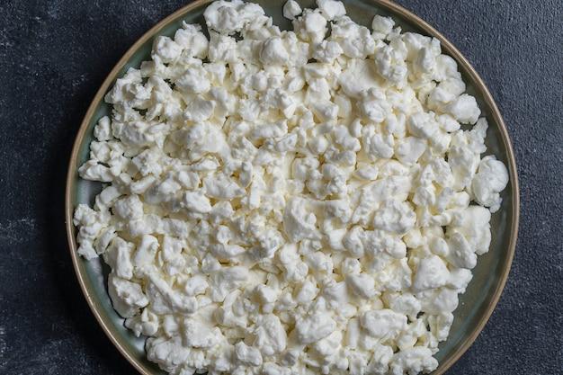 Творог в тарелке фона, вид сверху. белая зернистая текстура молочного продукта, творога заделывают. концепция молочного продукта