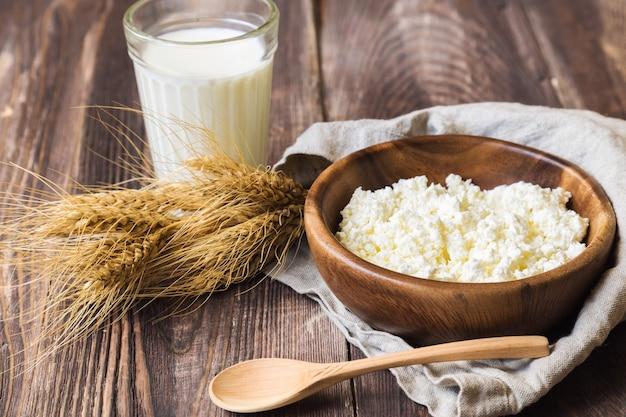素朴な木製の背景にカッテージチーズ、ミルク、小麦の穂。ユダヤ教の祝日シャブオットの乳製品。