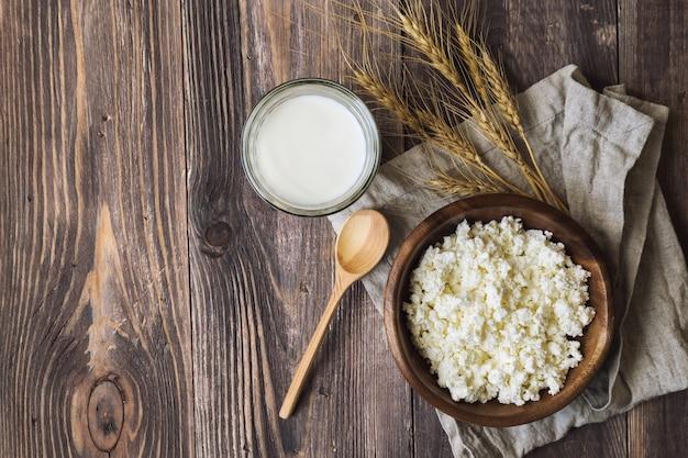 素朴な木の表面にカッテージチーズ、ミルク、小麦の穂。ユダヤ教の祝日シャブオットの乳製品。上面図。