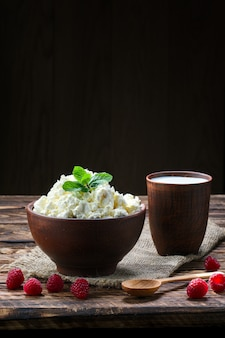 Cottage cheese and milk in clayware on wooden table