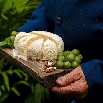 나무 쟁반에 있는 코티지 치즈, 포도, 호두, 노인 여성의 손에