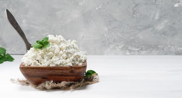 흰색 나무 배경에 민트 잎이 있는 전통적인 나무 그릇에 코티지 치즈 또는 부드러운 커드. 자연 건강 식품, 건강에 좋은 다이어트 식품. 클로즈업, 복사 공간이 있는 선택적 초점.