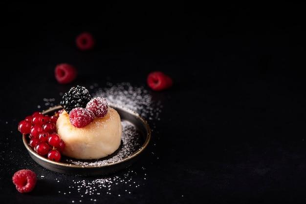 검은 접시에 딸기와 가루 설탕과 코티지 치즈 팬케이크 프리미엄 사진