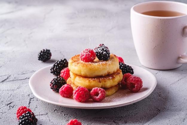 Творожные оладьи и творожные оладьи из сахарной пудры, десерт с ягодами малины и ежевики в тарелке рядом с чашкой горячего чая с ломтиком лимона на каменном бетонном фоне