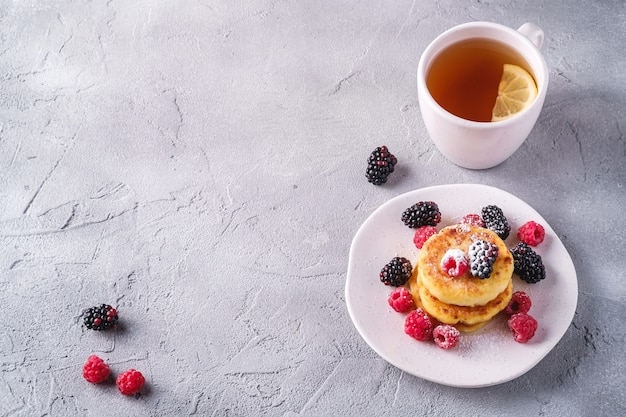 Творожные оладьи и сахарная пудра, творожные оладьи десерт с малиной и ягодами ежевики в тарелке рядом с чашкой горячего чая с ломтиком лимона