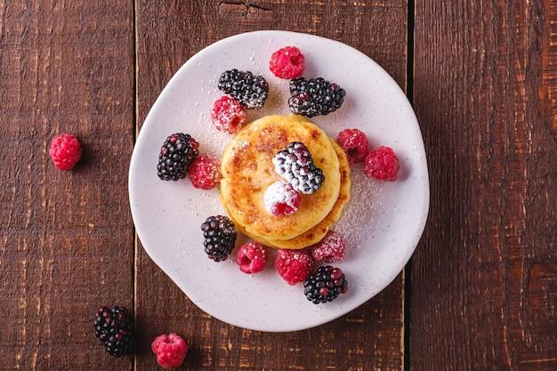 Творожные оладьи и сахарная пудра, десерт из творожных оладий с ягодами малины и ежевики в тарелке на темно-коричневом деревянном столе, вид сверху