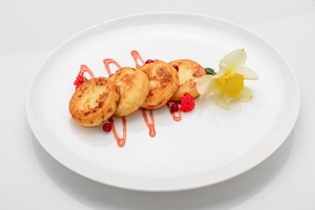 Творожные оладьи и клубничный соус, на белом фоне
