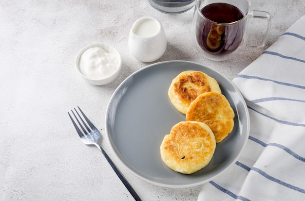 Cottage cheese pancakes on a black plate with cream, jam and cup of latte. healthy breakfast. homemade food