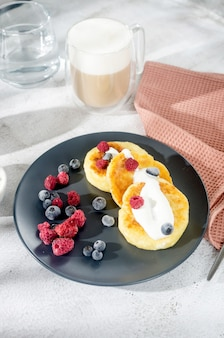 Cottage cheese pancakes on a black plate with frozen blueberries, strawberries and raspberries and cup of latte. healthy breakfast.