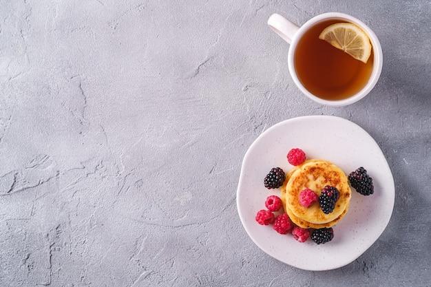 Творожные блины творожные оладьи десерт с ягодами малины и ежевики в тарелке рядом с чашкой горячего чая с ломтиком лимона на каменном бетонном фоне вид сверху копией пространства