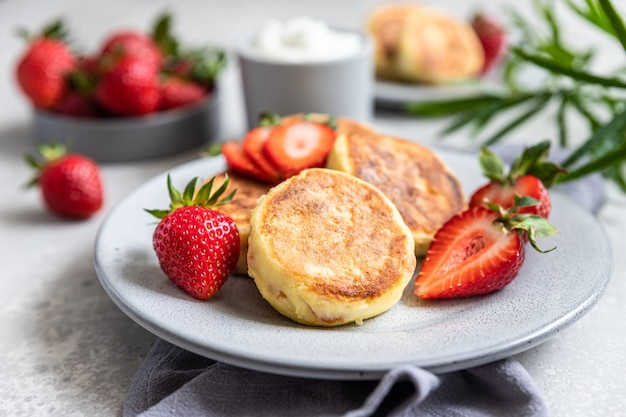 Cottage cheese pancakes or fritters with strawberry and natural yogurt